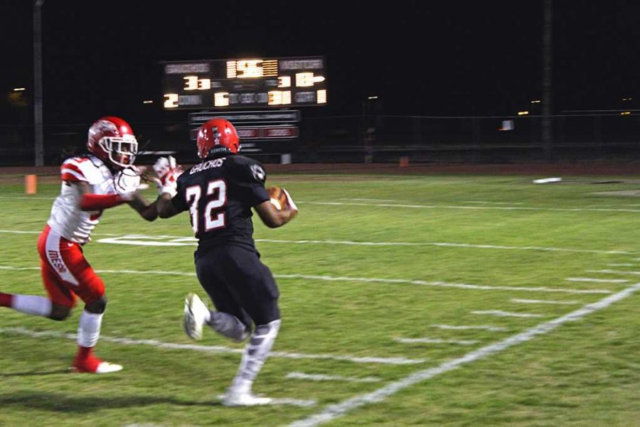GCC's Gregory Scott stiff-arms a defender before running out of bounds. Photo by Justin Pinzon/The Voice